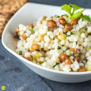 Sabudana ki khichri on a white bowl with some coriander leaves on it and some nuts spread on a wooden surface and a basket behind the bowl |