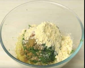 Potatoes, green paste, all spices and gram flour in bowl