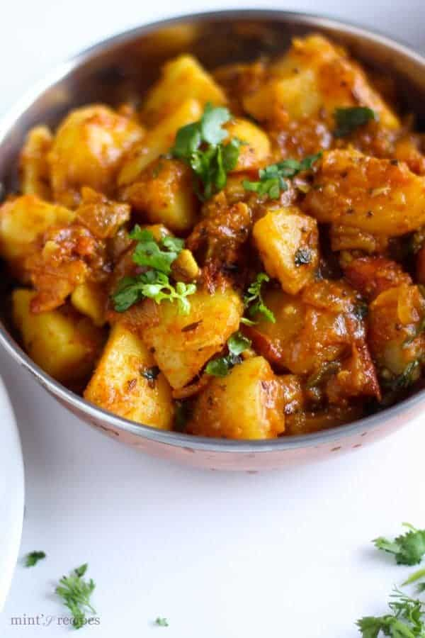 Spicy Potato Curry on a deep vessels garnished with some coriander leaves