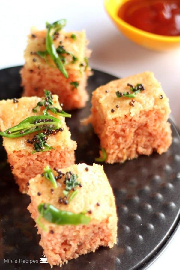 Suji Dhokla on a black plate with tempering of green chili and mustard seed |