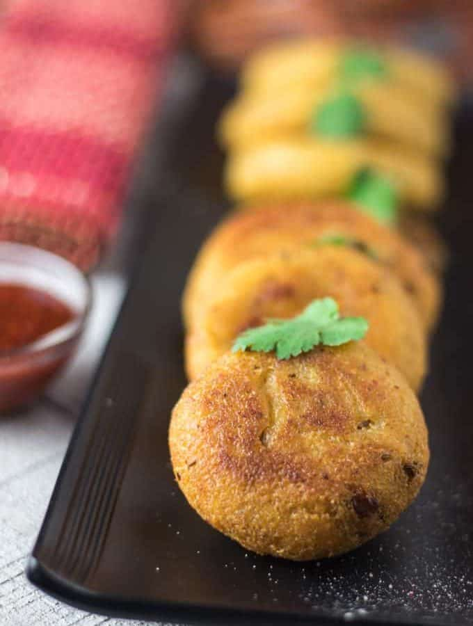 Suji ki kachori on a white plate with some green chutney garnish with coriander leaves