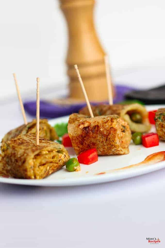 Suji Potato Rolls on a white plate with some chopped veggies like red bell pepper and green peas with some coriander leaves and some suji potato rolls in a black tray kept on a white surface |