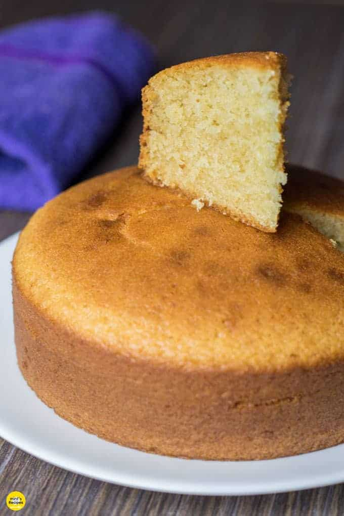 Eggless Vanilla Cake in a black plate with some gems on a white surface |