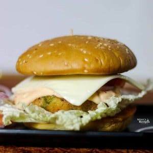 Vegetable Burgers on a black rectangular tray with some onion slices kept on a dark paper surface with dark background |