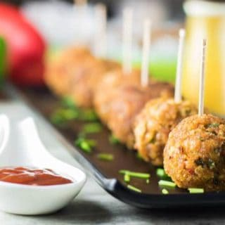 Veg Kurkure Lollipops on a white tray with some green chutney and tomato ketchup dips on the bckground and decorated with some coriander leaves and cornflakes| www.mintsrecipes.com |