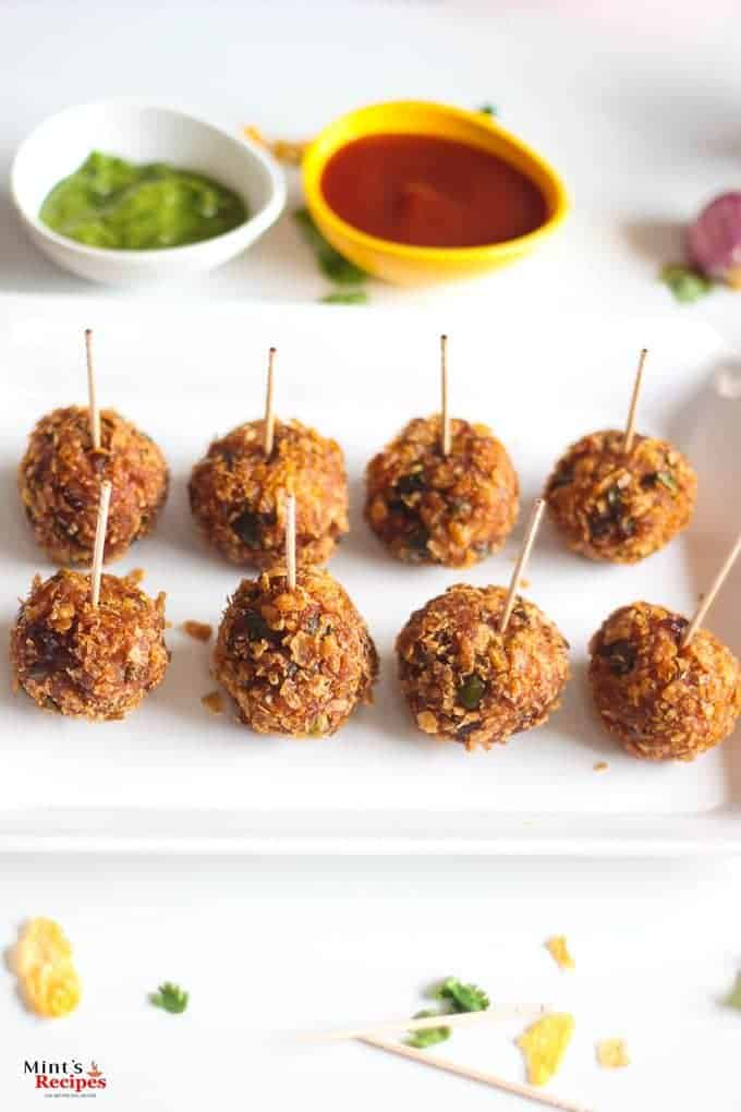 Veg Kurkure Lollipops on a white tray with some green chutney and tomato ketchup dips on the bckground and decorated with some coriander leaves and cornflakes|