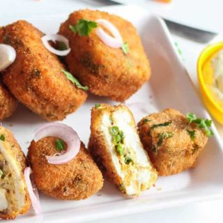 Veg Paneer Cheese Bites With Mayo Dip on a white plate with some onion rings and few coriander leaves with some mayonnaise dip|