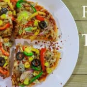 Veg Pizza On Tawa on a white plate with some sprinkles of chilli flakes kept on a wooden surface with a yellow bell pepper and a small bowl of red chilli flakes on the background |