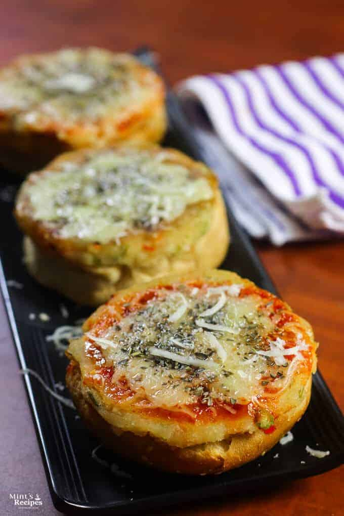 Veg Suji Buns on a black tray with some suji buns garnished with some cheese and oregano kept on a wooden surface |