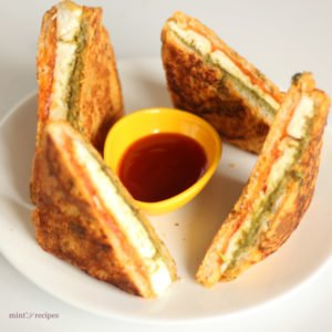 Bread Paneer Pakoda on a white plate with some tomato ketchup and green chutney on a small bowl kept on a dark mattress