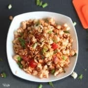 Popcorn Bhel on a white bowl with lots of veggies and sev for garnish.|