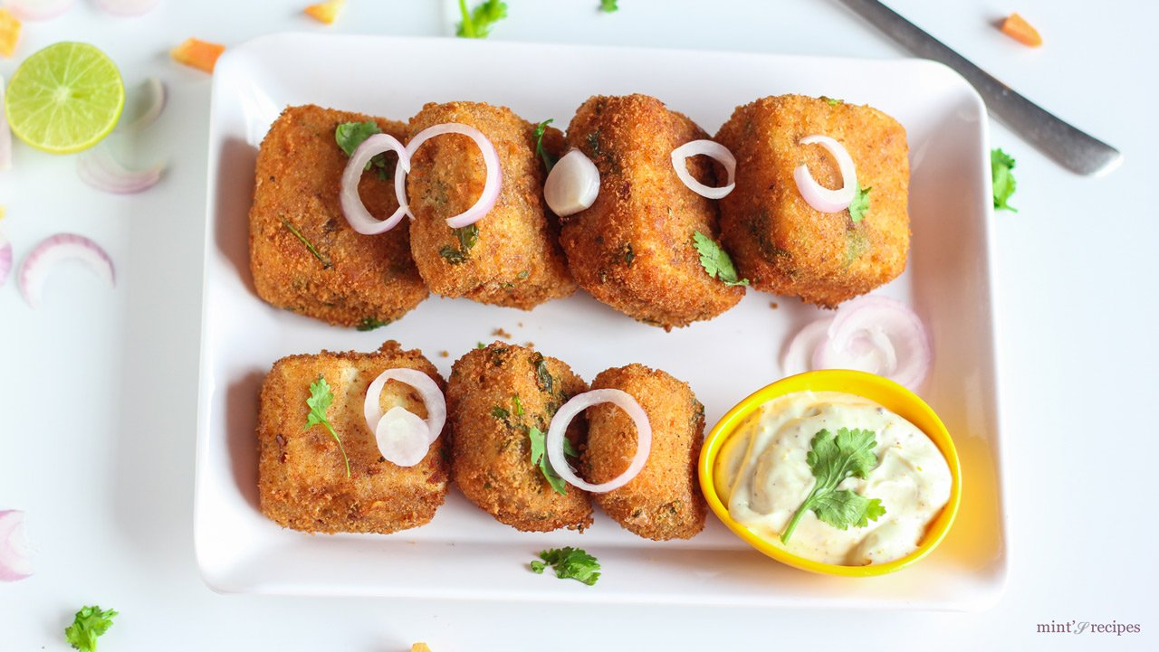 Veg Paneer Cheese Bites With Mayo Dip on a white plate with some onion rings and few coriander leaves with some mayonnaise dip 