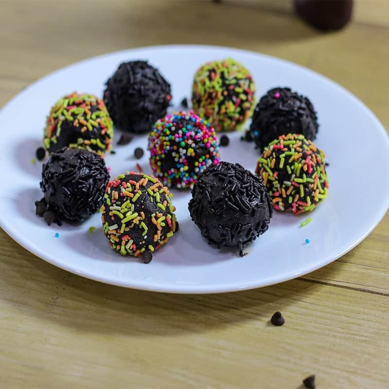 Chocolate Biscuit Balls on a white plate with some biscuit balls coated with colorful sprinklers