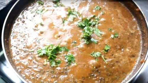Dal Makhani on a deep heavy pan on a white surface. garnished with butter and cream with some coriander leaves | www.mintsrecipes.com |