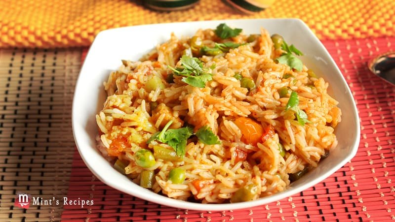 Vegetable Pulao on a tranparent plate garnished with some coriander