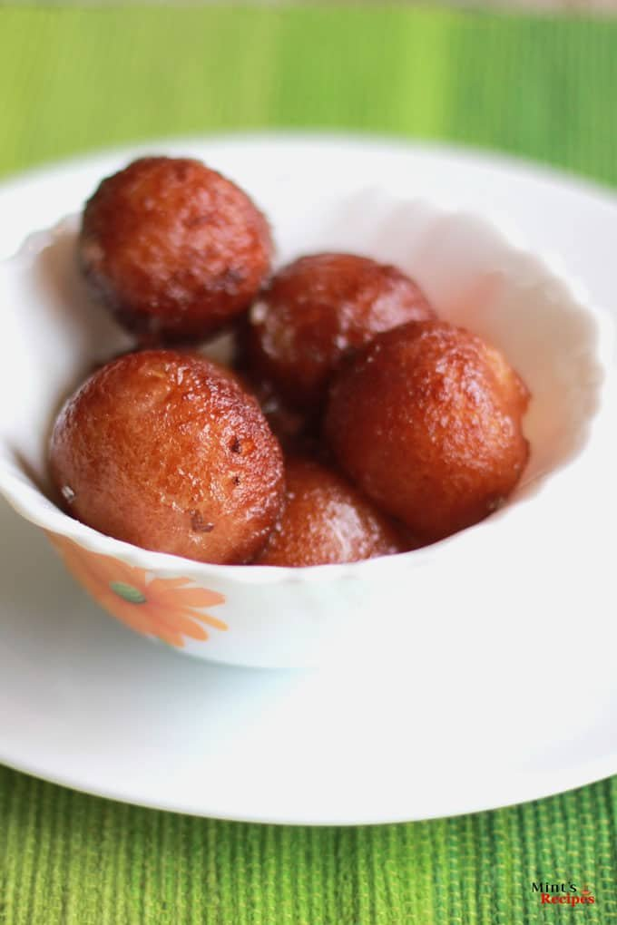 Bread gulab jamun on a white bowl putted on a white plate in a green coloured mat |