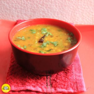 Turai chana dal on a red bowl garnished with some coriander