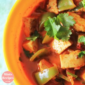 Kadhai Paneer on a yellow bowl with lots of veggies and garnished with coriander leaves
