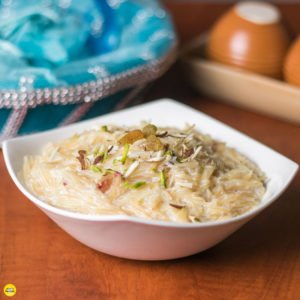 Sewai Kheer Recipe| Sewai served on a white bowl garnished With Almonds,Pistachious and raision Over A red mat lined With Black And Creamy Coloured Strings.