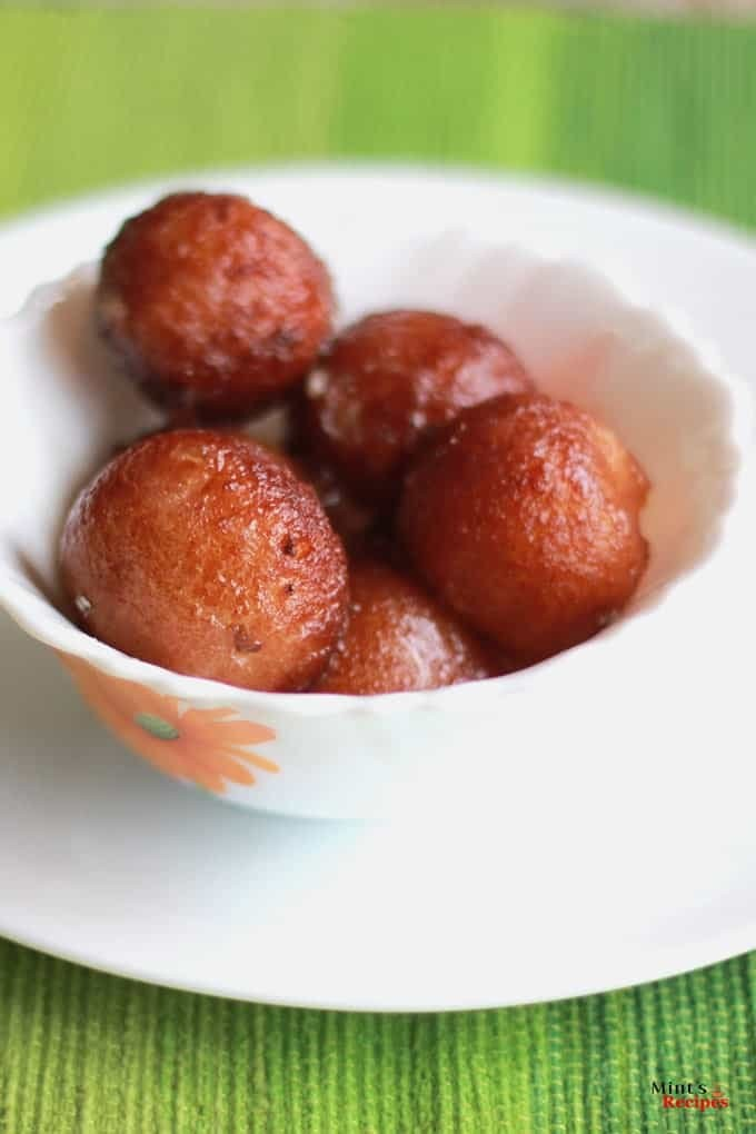 Bread gulab jamun on a white bowl putted on a white plate in a green coloured mat  