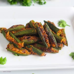 Bharwa Bhindi on a white bowl with some coriander leaves on the background kept on a wooden surface with a spoon
