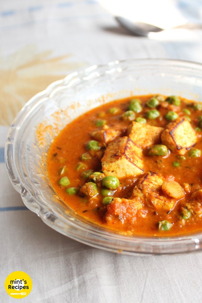 Matar Paneer on a transparent plate on a white surface