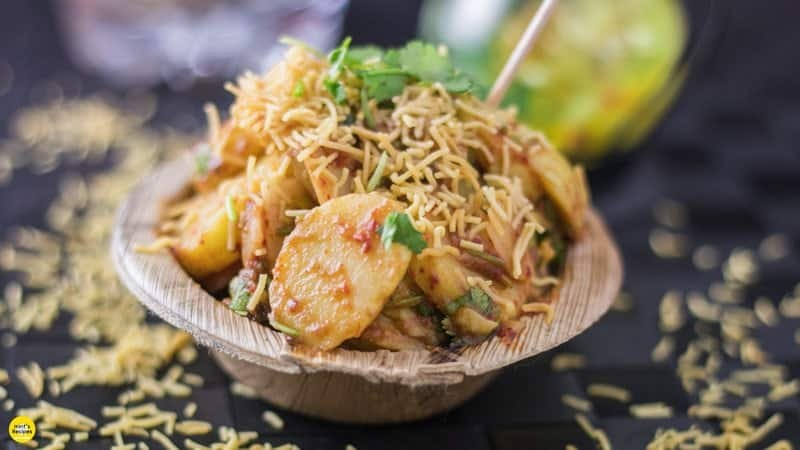 Aloo chaat on a disposable plate garnished with some sev and coriander leaves with a toothpick on a dark mat sprinkles with some sev  