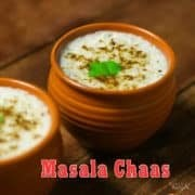 Masala Chaas in a clay pot with some cumin powder and coriander leaves and another masala chaas in the background kept on a wooden surface with some coriander leaves and chopped carrots to decorate the surface |