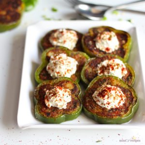 Capsicum Masala Tikki on a white tray with some coriander leaves and green peas