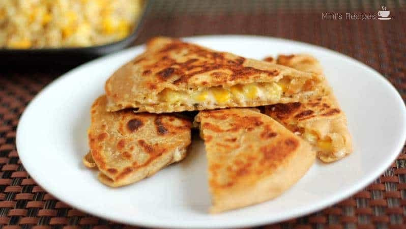 Cheese Corn Pizza Paratha on a white plate with dark background with some cheese corn mixture |
