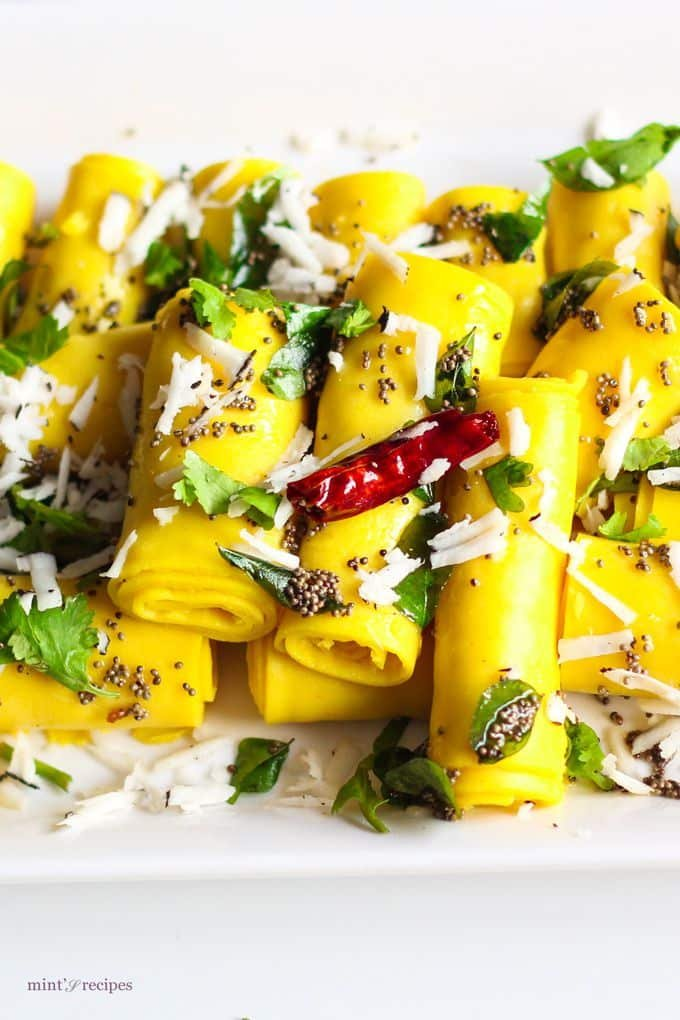 Khandvi on a white plate, garnished with some tempering of mustard seed and grated coconuts