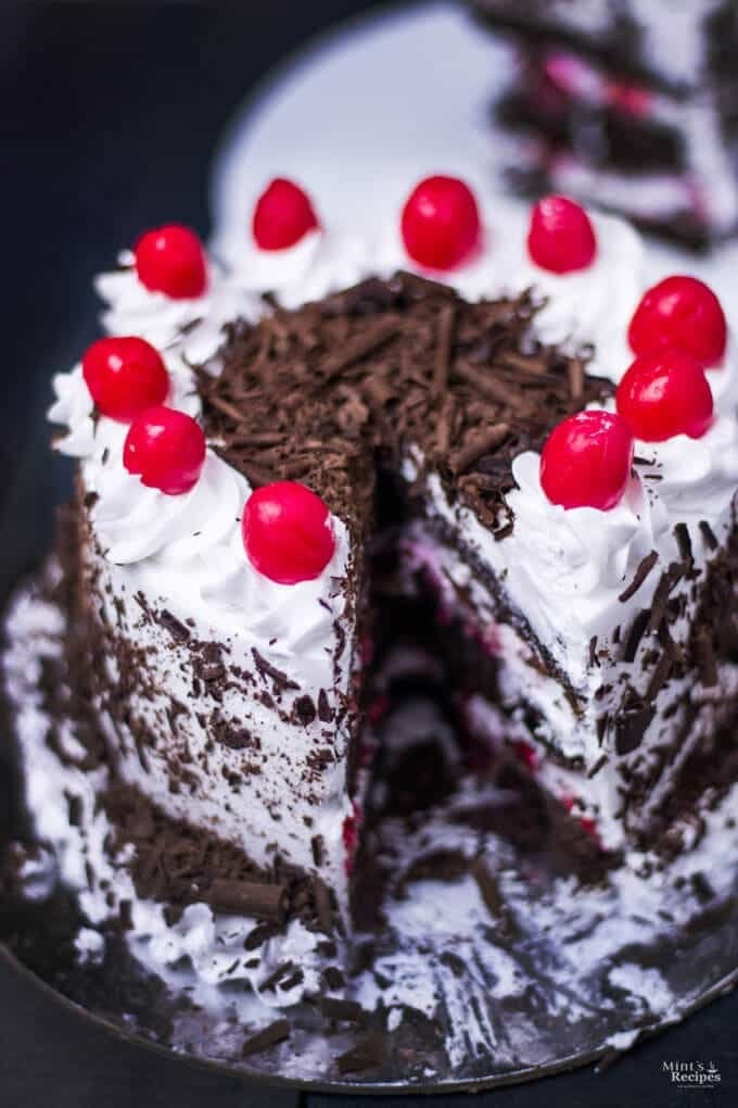 Black Forest Cake with cherries on top with a slice of blackforest cake on a white plate in dark background |