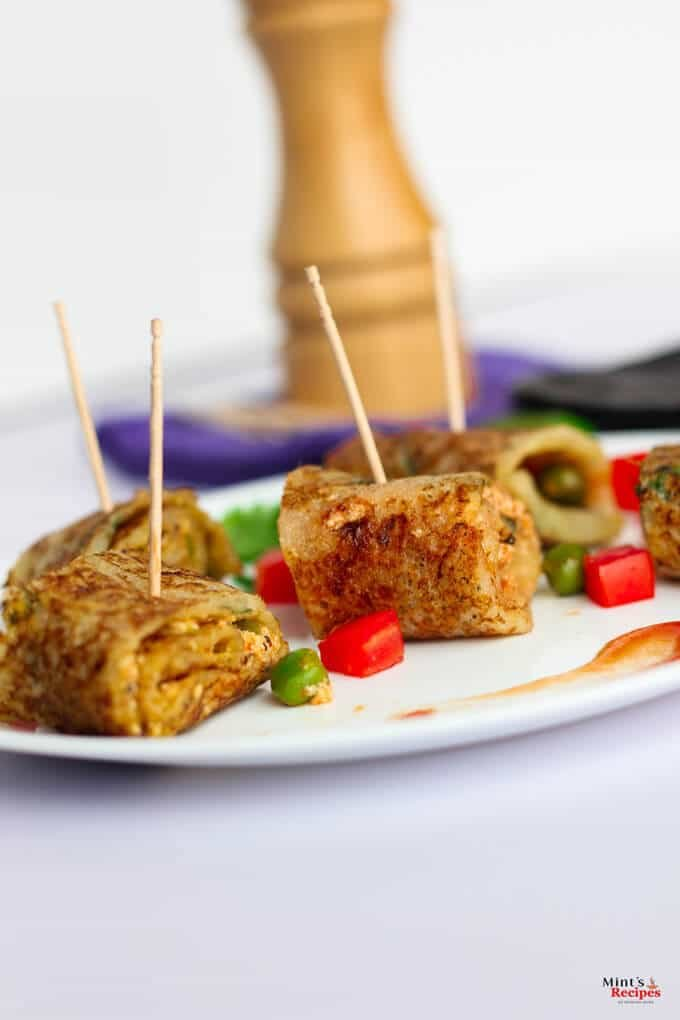 Suji Potato Rolls on a white plate with some chopped veggies like red bell pepper and green peas with some coriander leaves and some suji potato rolls in a black tray kept on a white surface  