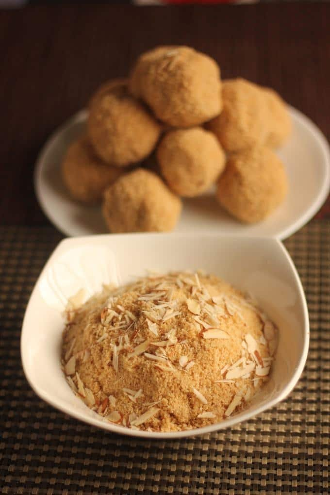 Rajasthani Churma Laddoo on a white plate putted on a mat and a bowl full of churma with some almonds garnished on it |