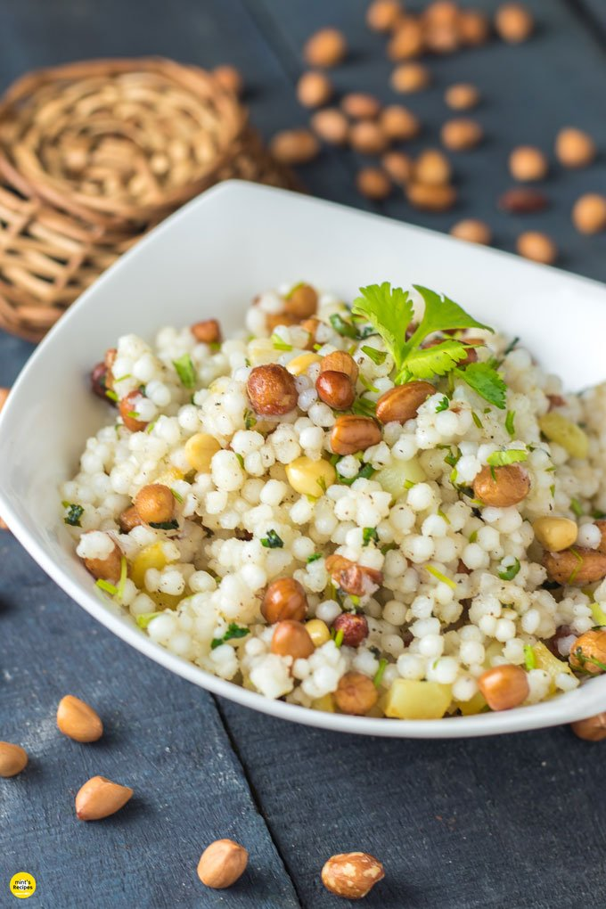 Sabudana ki khichri on a white bowl with some coriander leaves on it and some nuts spread on a wooden surface and a basket behind the bowl