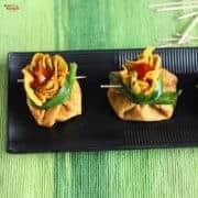 Besan Chilla Potli On a black rectangular tray with some chilla potli on it with some garnishing of spring onion and tomato ketchup kept on a green mattress with some toothpick around it  