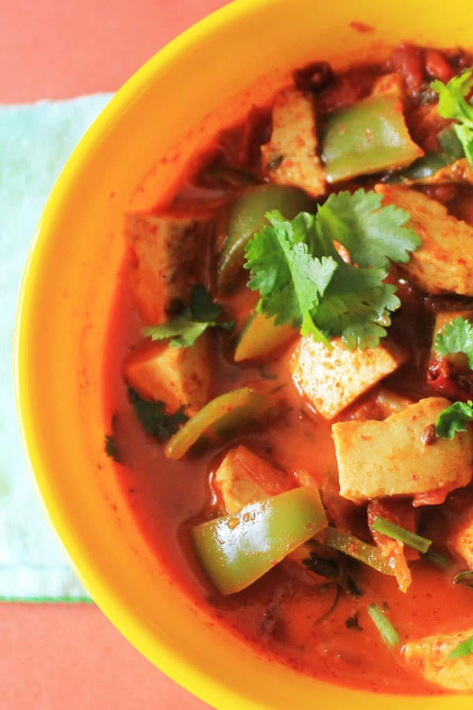 Kadai Paneer served on a yellow bowl with lots of veggies and garnished with coriander leaves