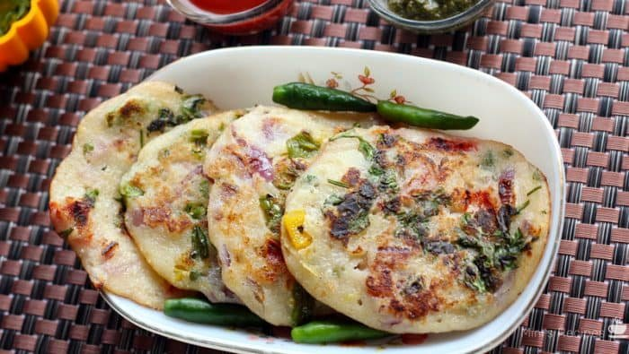Bread Uttapam On a white bowl with some garnishing of coriander leaves and green chilli, with some green chutney and tomato sauce| www.mintsrecipes.com |