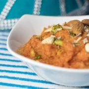 Gajar ka Halwa on a glass bowl garnished with chopped almonds and cashews | www.mintsrecipes.com |