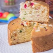 Tutti frutti Cake on a white plate with a slice cut of cake on the top of rest of the cake  