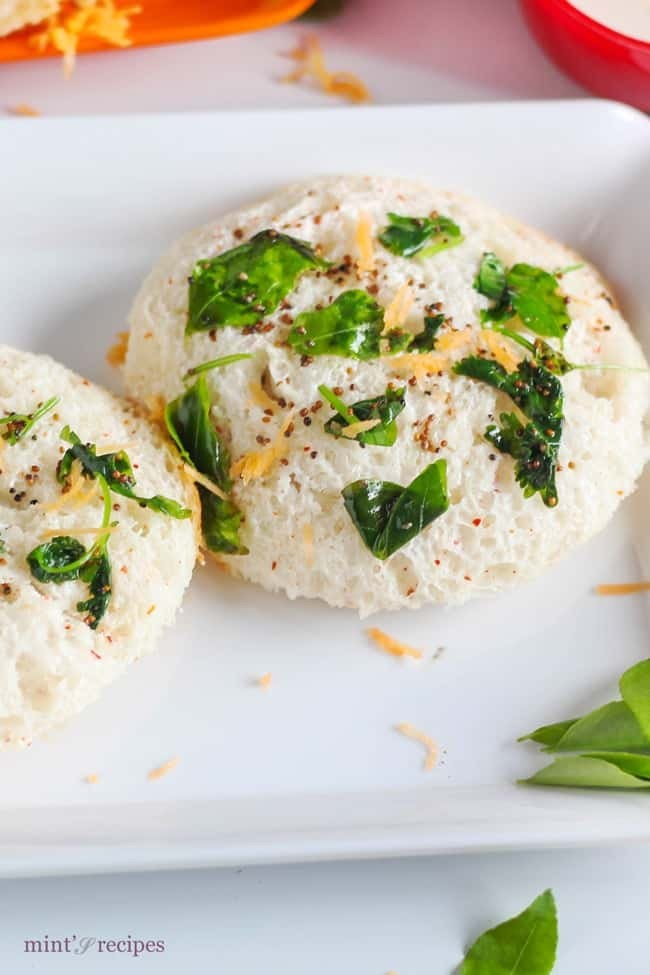 Bread Idli on a white tray with some tempering of mustard seed