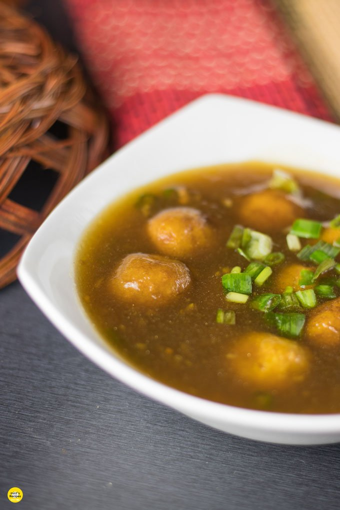 Potato Manchurian On a white bowl with some spring onions on top for garnishing and a wooden bowl with some mat on the background  