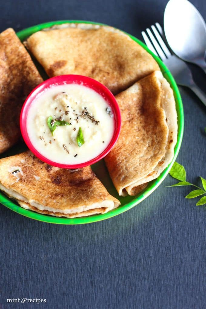 Oats Poha Dosa on a round plate with 4 pieces of oats dosa on it with a small bowl of coconut chutney and little tempering of mustard seed and curry leaves putted on a dark surface with spoon and fork and some curry leafs |