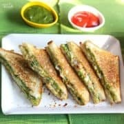Veg Mayonnaise Sandwich Recipe on a white tray with chilli flakes and some green chutney and tomato ketchup on the background |
