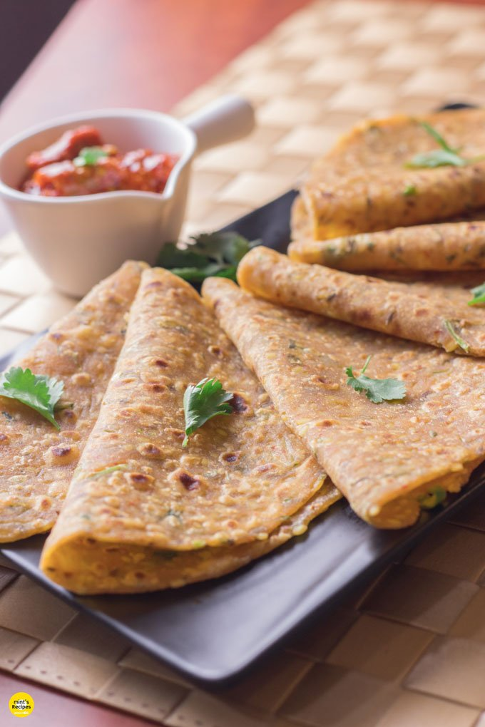 Sabut moongdal ka paratha on a black tray with some coriander leaves