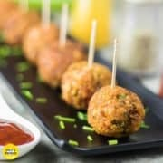 Veg Kurkure Lollipops on a white tray with some green chutney and tomato ketchup dips on the bckground and decorated with some coriander leaves and cornflakes 