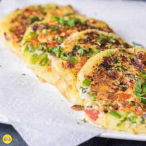Bread Moongdal Uttapam on a white plate in absorbent paper|