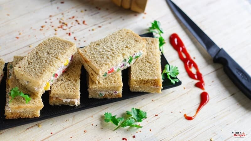 Cream Cheese Sandwich on a black plate for garnishing some coriander leaves and some chilli flakes| www.mintsrecipes.com |