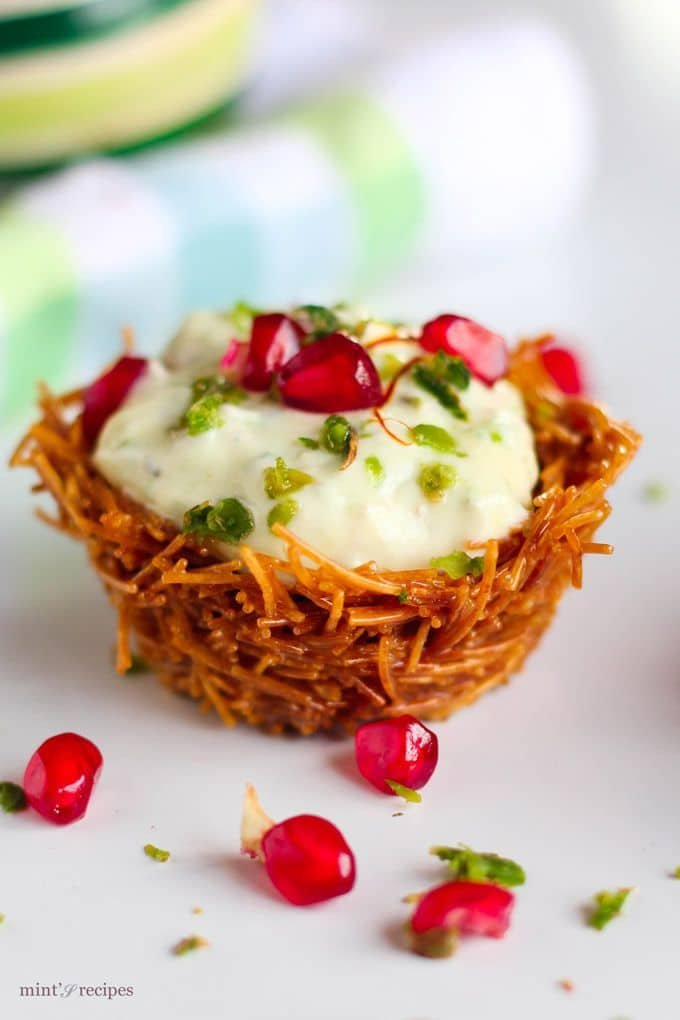 Hung curd mixture placed on a vermicelli tokri with some pomogranate and pista to garnish