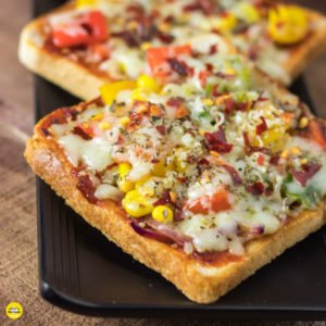 Bread pizza on a black plate garnish with oregano